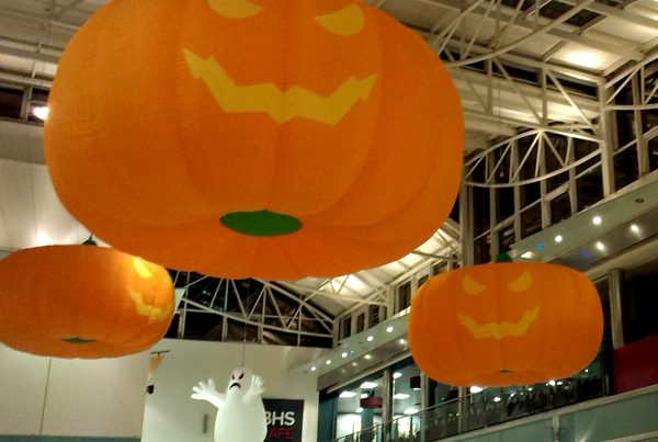 Halloween installation with giant-size pumpkins and ghosts suspended from the ceiling