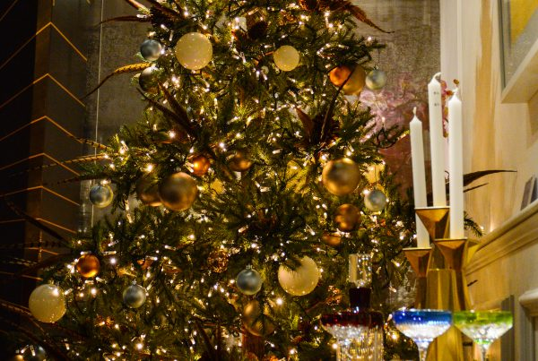Ornately decorated Christmas tree with gold baubles and warm lighting